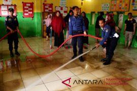 Membersihkan sekolah dari lumpur banjir