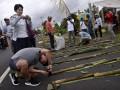 Wisatawan Tiongkok mengambil detail foto nasi jaha yang dijajarkan sepanjang jalan di Tomohon, Sulawesi Utara, Senin (7/8).  Kegiatan dalam rangka Tomohon International Flower Festival (TIFF) 2017 tersebut menghabiskan 15.165 liter beras, 10.110 butir kelapa untuk bahan santan serta 20.220 batang bambu yang dibentangkan sepanjang 12 km, yang berhasil mendapatkan rekor MURI kategori Nasi Jaha terpanjang. ANTARA FOTO/Adwit B Pramono/aww/17.