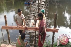 Bhabinkamtibmas bersama warga Kampung Sanggase perbaiki jembatan