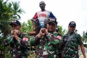 Prajurit TNI tandu pasien menuju lokasi pengobatan