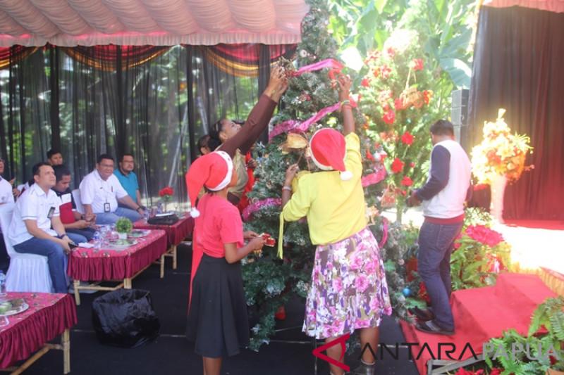 Anak-anak panti asuhan hias pohon Natal