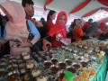 Seorang pengunjung mengambil salah satu olahan berbahan jagung yang dipamerkan ketika digelar rekor MURI di Palu, Sulawesi Tengah, Minggu (16/4). Sebanyak 317 menu olahan serba jagung tersebut dicatat dalam rekor MURI. ANTARA FOTO/Fiqman Sunandar)