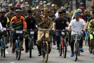 Presiden dandan ala pejuang kemerdekaan mengayuh sepeda