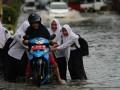Beberapa anak sekolah membantu mendorong pengendara yang terjebak banjir di jalan Supu Yusuf, Kecamatan Mandonga, Kendari, Sulawesi Tenggara, Selasa (28/2). Lima Kecamatan di Kendari terendam banjir saat beberapa jam diguyur hujan, drainase yang buruk dan pembangunan pertokoan tidak teratur menjadi salah satu penyebabnya. ANTARA FOTO/Jojon/17.