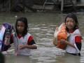Pelajar melintasi banjir menuju rumahnya sepulang dari sekolah di Kendari, Sulawesi Tenggara, Kamis (30/3). Tingginya intensitas curah hujan mengakibatkan ratusan rumah di Kendari terendam banjir. ANTARA FOTO/Jojon/aww/17.
