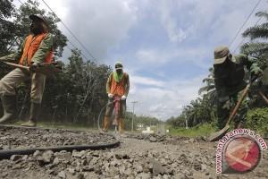 Anggota polisi tambal jalan lintas pantai timur Sumatera
