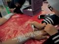 Seniman henna mengukir tangan model dengan henna putih pada kompetisi Henna Art Palembang di OPI Mall Palembang, Sumatra Selatan, Minggu (18/6). Puluhan seniman henna beradu ide dan keterampilan dalam kompetisi dengan tema motif khas Palembang baik berupa motif songket, ukiran, maupun lakuer. (Antarasumsel.com/Feny Selly/Ag/17)