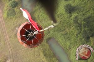 Helikopter BNPB Kibarkan Bendera Merah Putih