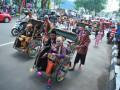 Pasangan peserta nikah massal berbahagia saat mengikuti pawai menuju Rumah Dinas Walikota di Jalan Tasik, Palembang, Sumatera Selatan, Kamis (12/10). Sebanyak 35 pasangan pengantin mengikuti kegiatan nikah massal yang diselenggarakan Pemerintah Kota Palembang yang bertujuan untuk membantu kesulitan biaya pengurusan administrasi kelegalan pernikahan. (ANTARA Sumsel/Feny Selly/Ang/17)